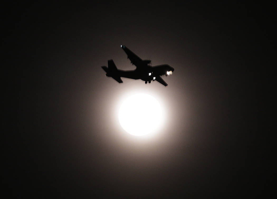 An airplane passes the full moon on its final approach before landing in Seoul, South Korea, Wednesday, Jan. 31, 2018. The moon is putting on a rare cosmic show. It's the first time in 35 years a  ...