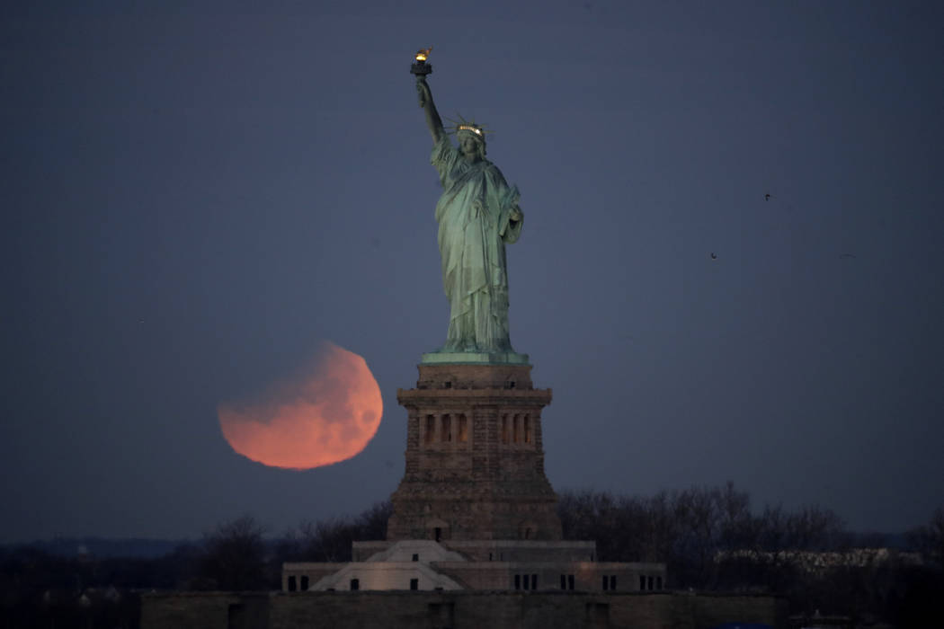 The Statue of Liberty is backdropped by a supermoon, Wednesday, Jan. 31, 2018, seen from the Brooklyn borough of New York. The supermoon, which is the final of three consecutive supermoons, also e ...