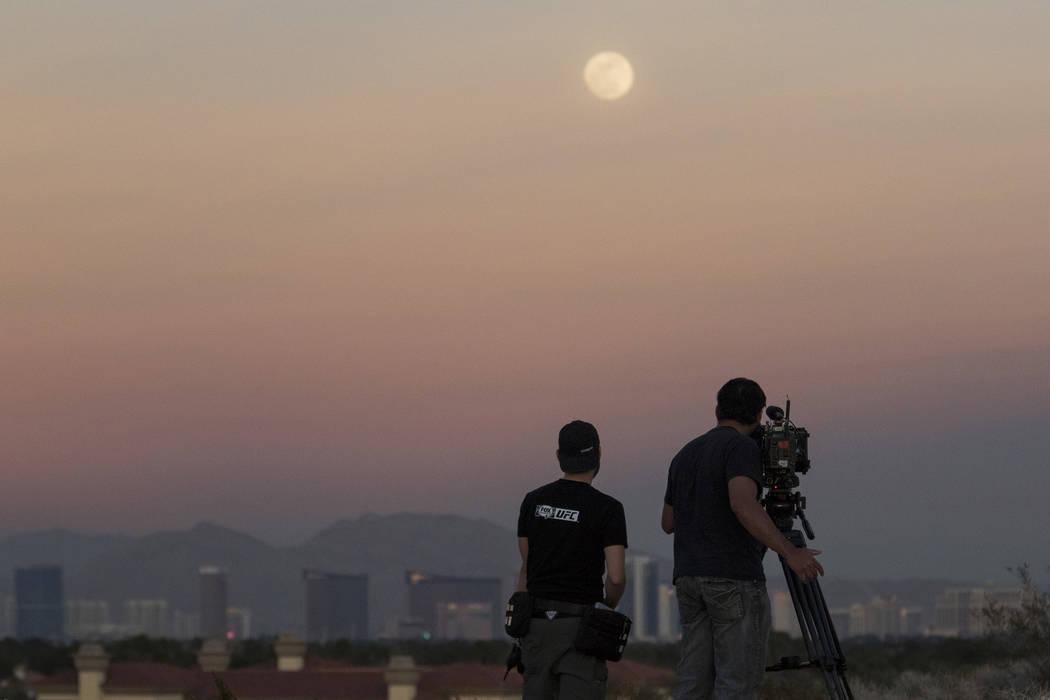 Ultimate Fighter Championship videographers Chris Warner, left, and Silton Buen Dia film the moon in Las Vegas on Tuesday, Jan 30, 2018. (Richard Brian/Las Vegas Review-Journal via AP)