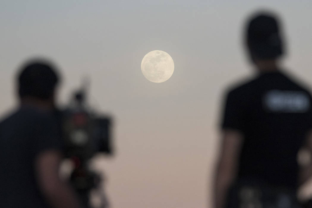 Ultimate Fighter Championship videographers Silton Buen Dia, left, and Chris Warner film the moon in Las Vegas on Tuesday, Jan 30, 2018. (Richard Brian/Las Vegas Review-Journal via AP)