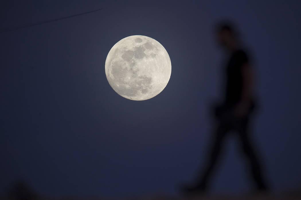 Ultimate Fighter Championship videographer Chris Warner walks past the moon as he films b-roll in Las Vegas on Tuesday, Jan 30, 2018. (Richard Brian/Las Vegas Review-Journal via AP)
