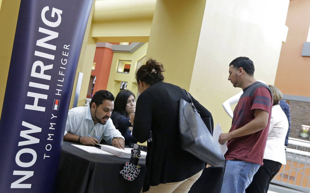 FILE - In this Tuesday, Oct. 3, 2017, file photo, job seekers stand at a booth at a job fair at the Dolphin Mall in Sweetwater, Fla.  U.S. businesses kept hiring at a healthy pace in January 2018, ...