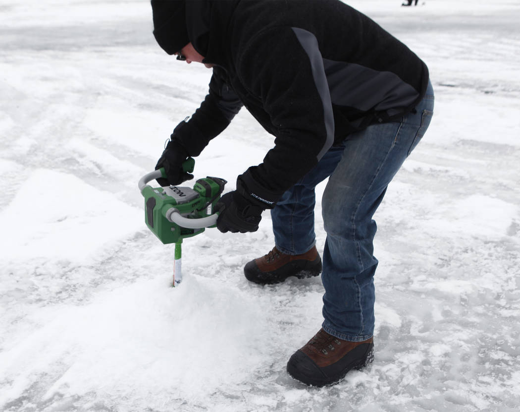 Long-time Minnesota Vikings fan Reg Proulx cuts through the ice at Lake Peltier in order to go ice fishing during Super Bowl LII week in Anoka County, Minn., Tuesday, Jan. 30, 2018. Heidi Fang Las ...