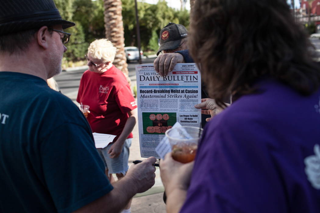 Dave Allen of Las Vegas, 68, center, holds a newspaper prop as George Bidwell, 61, left, and Marie Bidwell, 54, right, both of Scranton, Pa., scan it for clues during the Alibi Las Vegas in Las Ve ...