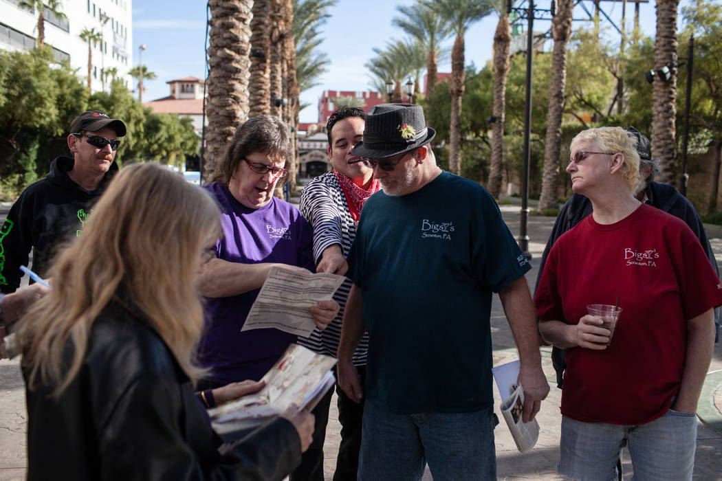 Mime artist Ren Bautista, center, points to a paper with clues as Marie Bidwell, 54, left, and her husband George Bidwell, 61, right, both of Scranton, Pa., pay attention during the Alibi Las Vega ...