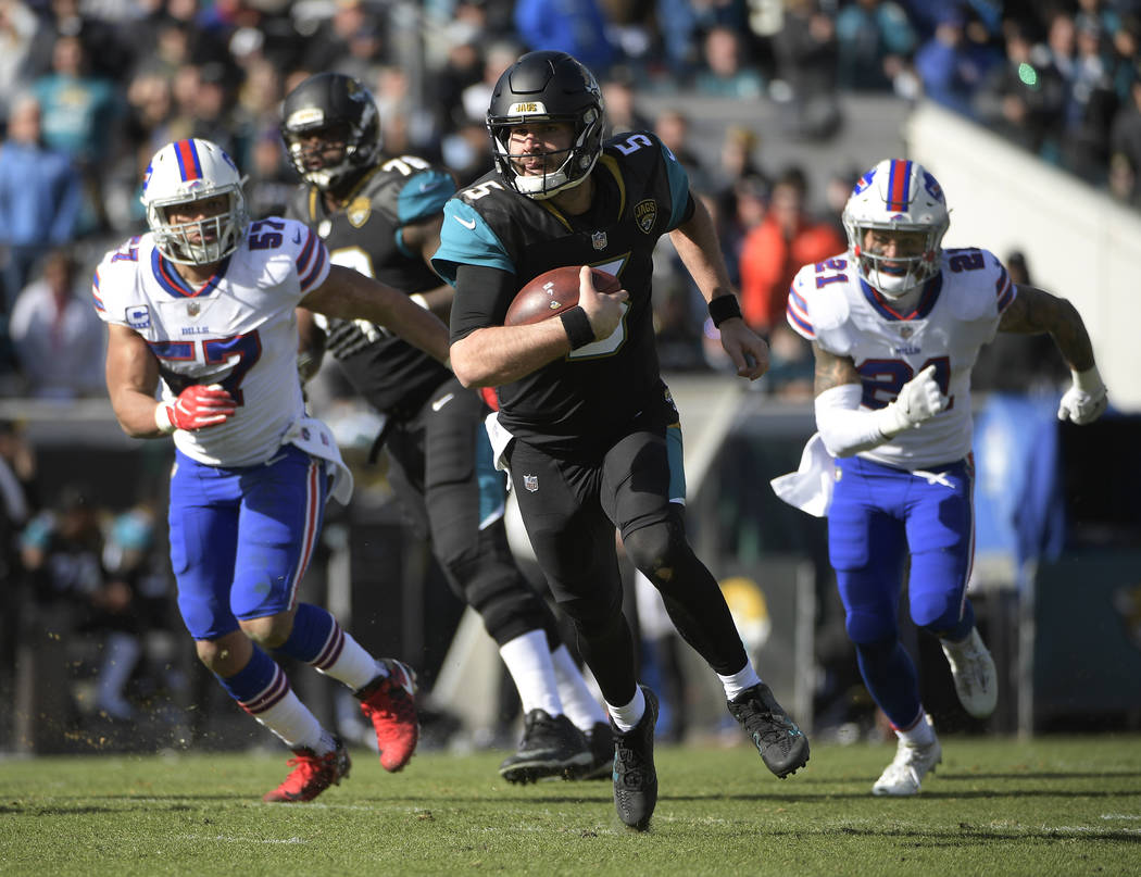 Jacksonville Jaguars quarterback Blake Bortles (5) rushes for yardage past Buffalo Bills outside linebacker Lorenzo Alexander (57) and free safety Jordan Poyer (21) in the first half of an NFL wil ...