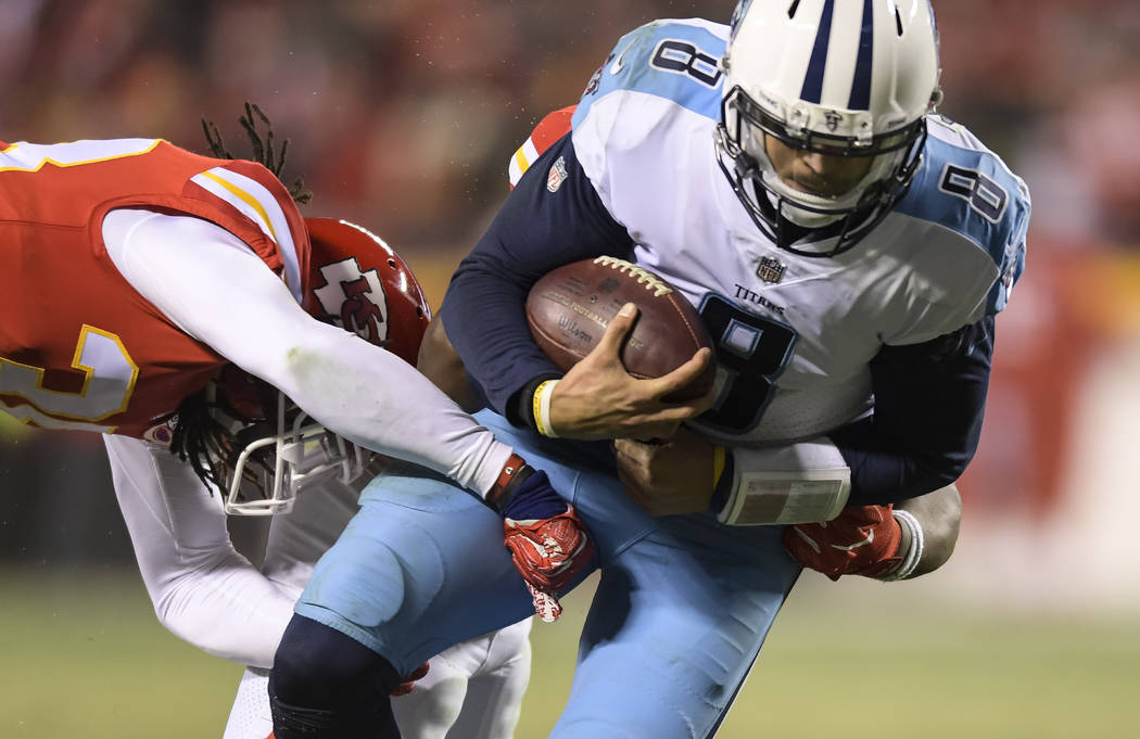 Tennessee Titans quarterback Marcus Mariota (8) is tackled by Kansas City Chiefs free safety Ron Parker (38) and Kansas City Chiefs outside linebacker Justin Houston (50) during the second half of ...