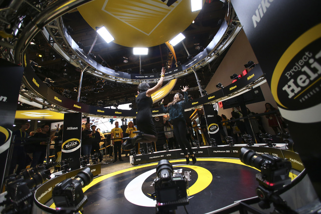 Attendees jump for a photo at the Nikon booth during CES at the Las Vegas Convention Center in Las Vegas on Friday, Jan. 6, 2017. (Chase Stevens/Las Vegas Review-Journal) @csstevensphoto
