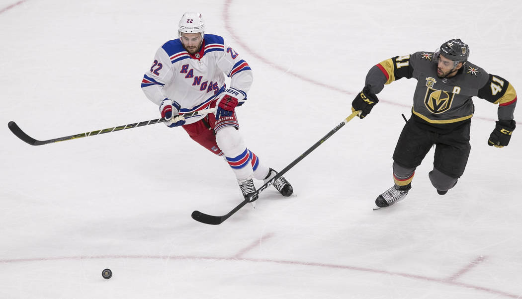 New York Rangers defenseman Kevin Shattenkirk (22) and Vegas Golden Knights left wing Pierre-Edouard Bellemare (41) chase a loose puck during the first period of an NHL hockey game between the Veg ...