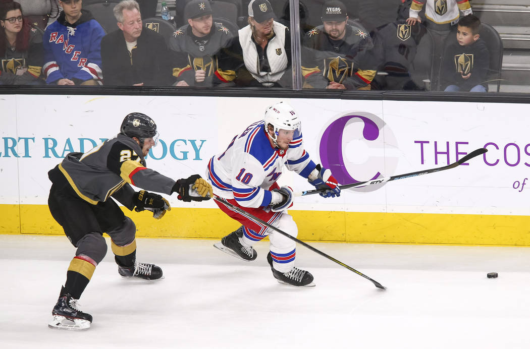 New York Rangers defenseman Marc Staal (18) and Vegas Golden Knights defenseman Shea Theodore (27) chase the puck during the third period of an NHL hockey game between the Vegas Golden Knights and ...