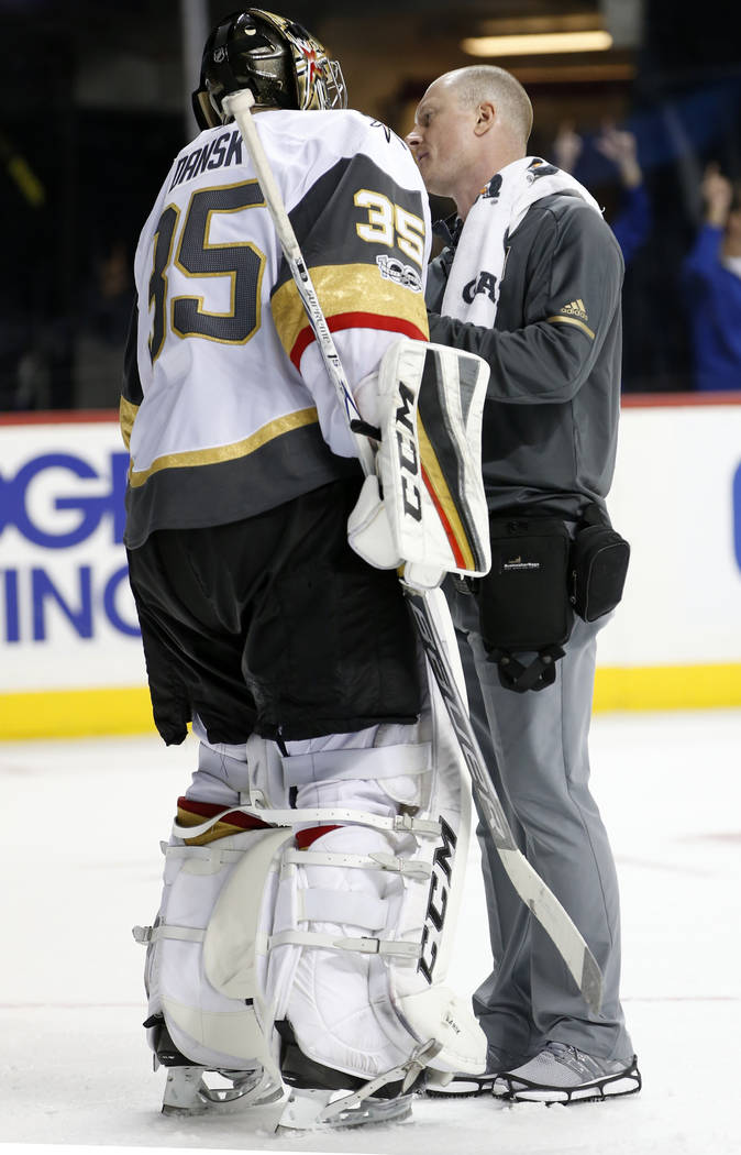 A trainer looks at Vegas Golden Knights goalie Oscar Dansk (35) of Sweden who left the game with an apparent injury during the second period of an NHL hockey game in New York, Monday, Oct. 30, 201 ...