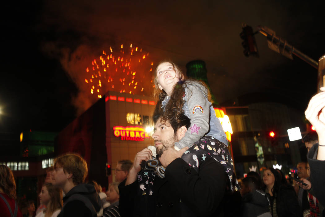 Paisley Tanabe, 8, sits on her father Miguel Alacala, 32, both of P[hoenix, Ariz., as fireworks go off along the Strip during the first minutes of New Year's Day in Las Vegas, Monday, Jan. 1, 2018 ...