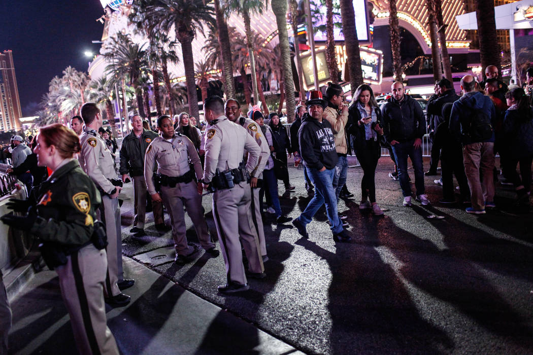 People walk past officers as they stand guard along the Strip on New Year's Eve in Las Vegas, Sunday, Dec. 31, 2017. Joel Angel Juarez Las Vegas Review-Journal @jajuarezphoto