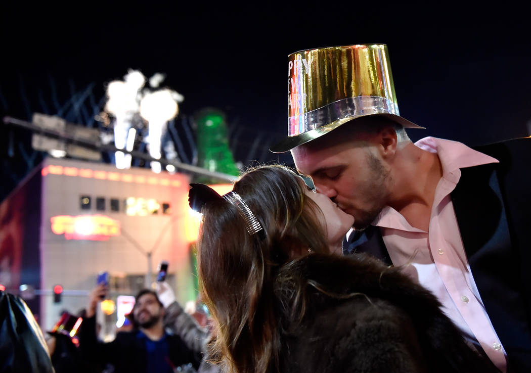 Breanna Vereeke and Graham Gugino of Mich. kiss as they bring in the new year along the Las Vegas Strip Monday, Jan. 1, 2018, in Las Vegas. David Becker/Las Vegas News Bureau