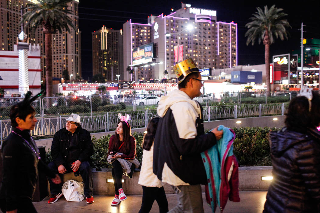 Martin Contreras, 64, left, and Melissa Contreras, 20, right, both of Los Angeles, take a break on New Year's Eve along the Strip in Las Vegas, Sunday, Dec. 31, 2017. Joel Angel Juarez Las Vegas R ...