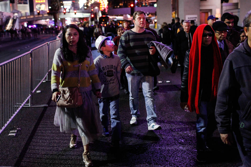 Yan Run Yang, 35, left, her son Jameson Wells, 9, center, and husband Ryan Wells, 42, right, all of Las Vegas, walk along the Strip on New Year's Eve in Las Vegas, Sunday, Dec. 31, 2017. Joel Ange ...