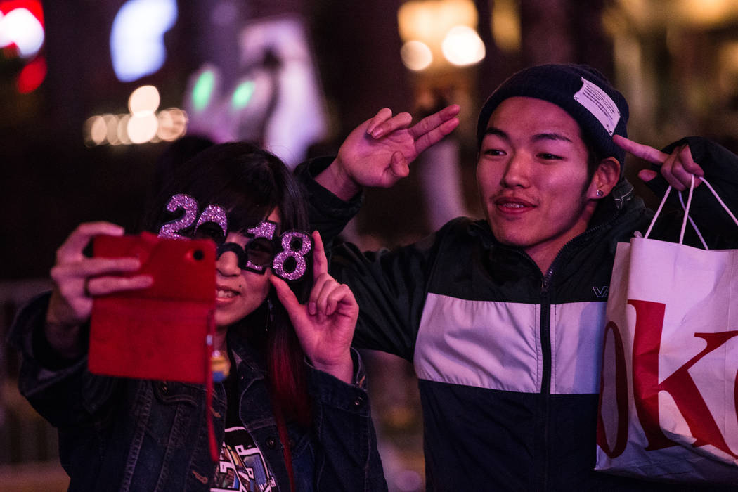 Maiko Oda of Hyogo, Japan, 27, left, and Tomoya Hirao of Hokkaido, Japan, 27, right, take a picture along the Strip on New Year's Eve in Las Vegas, Sunday, Dec. 31, 2017. Joel Angel Juarez Las Veg ...