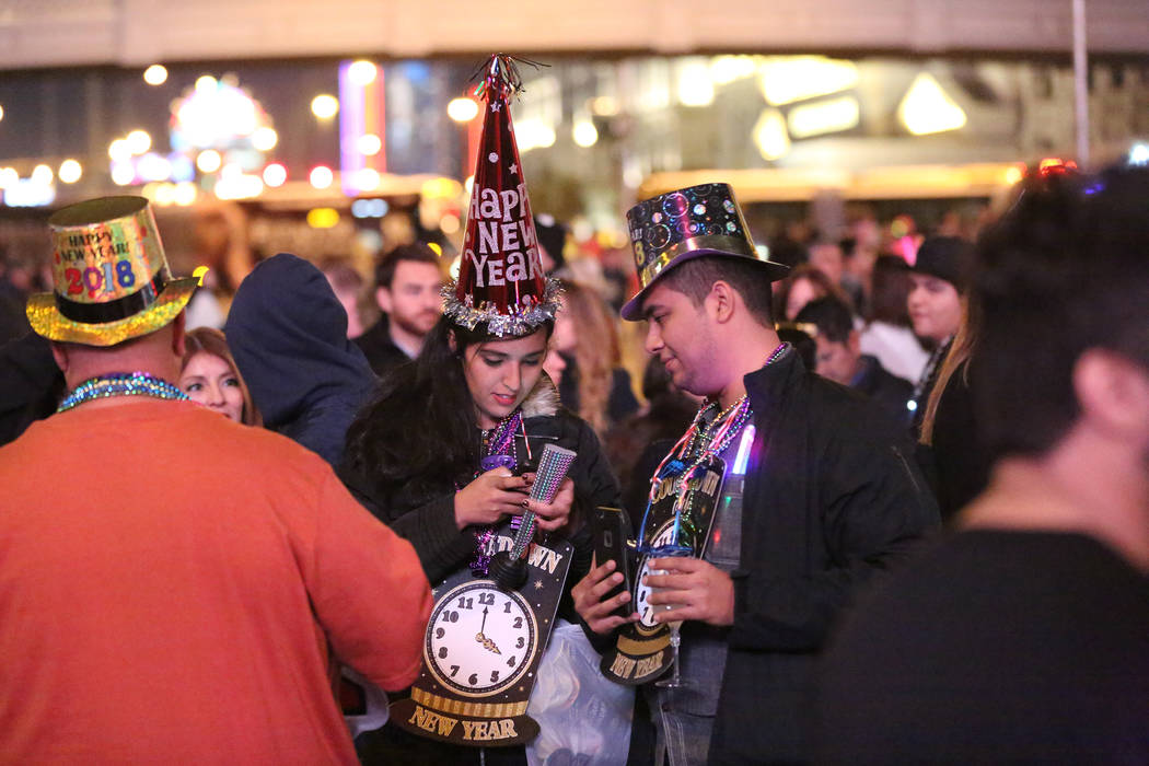 Anna Garcia and William Argaez of Cancun, Mexico check in on social media as they await the New Year's Eve  fireworks show on the Las Vegas strip on Sunday, Dec. 31, 2017. Michael Quine Las ...