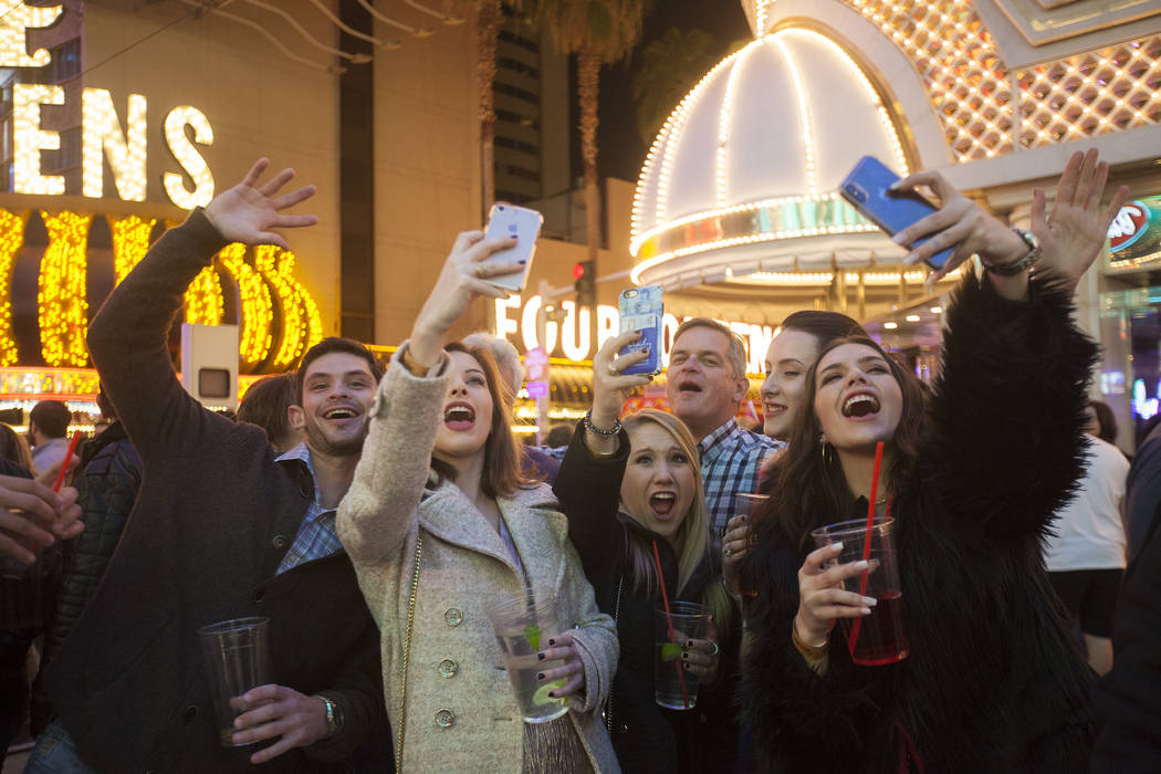 Travis Schauer, from left, Jill Schauer, Stephanie Hinge, Nicki Schauer, and Allyson Schauer FaceTime their friends back in Texas who were celebrating New Year's Eve their time at the Fremont Stre ...
