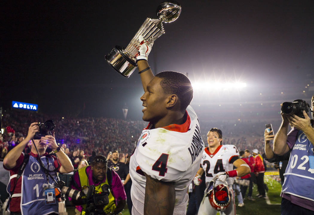 Georgia Bulldogs wide receiver Mecole Hardman (4) raises the Rose Bowl trophy after his team's double overtime defeat against the Oklahoma Sooners in the College Football Playoff semifinal at the  ...