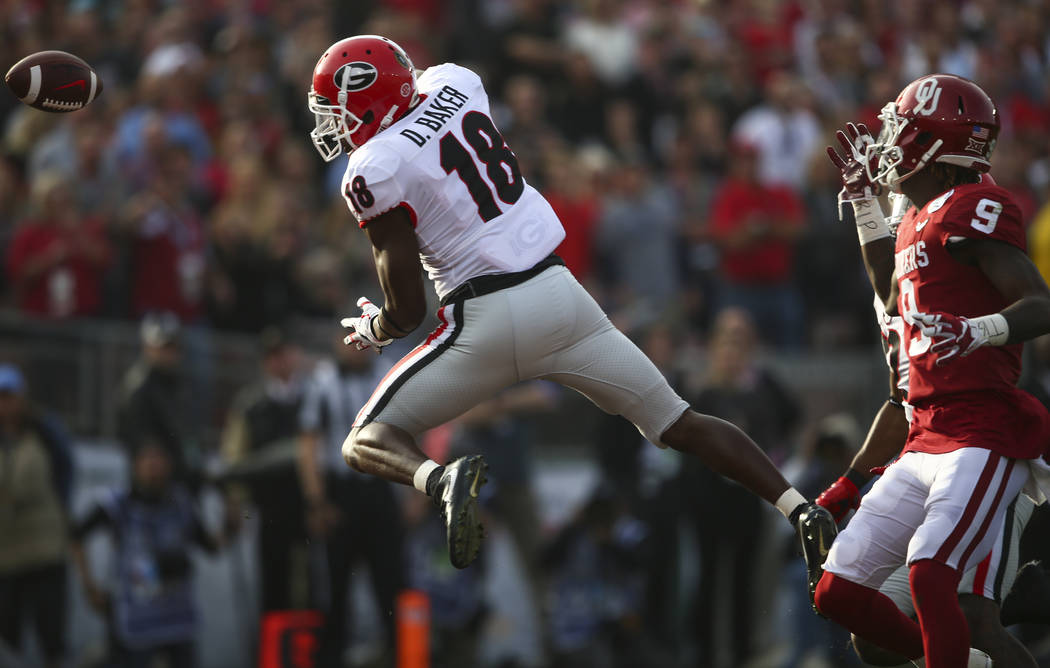 Georgia Bulldogs defensive back Deandre Baker (18) breaks up a pass intended for Oklahoma Sooners wide receiver CeeDee Lamb (9) during the first half of the College Football Playoff semifinal at t ...