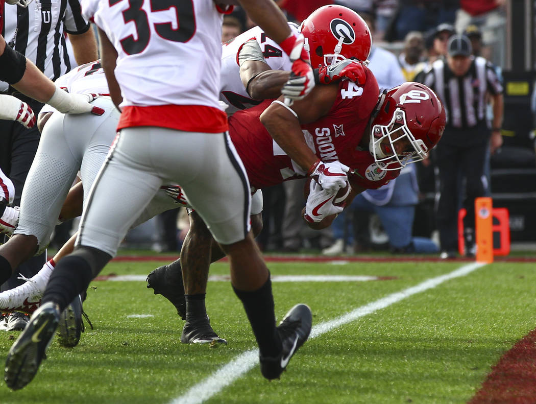 Oklahoma Sooners running back Rodney Anderson (24) leaps into the end zone to score a touchdown against the Georgia Bulldogs during the first half of the College Football Playoff semifinal at the  ...
