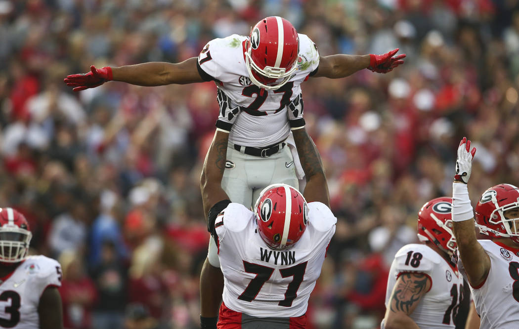 Georgia Bulldogs running back Nick Chubb (27) celebrates his touchdown with Georgia Bulldogs offensive tackle Isaiah Wynn (77) during the second half of the College Football Playoff semifinal agai ...