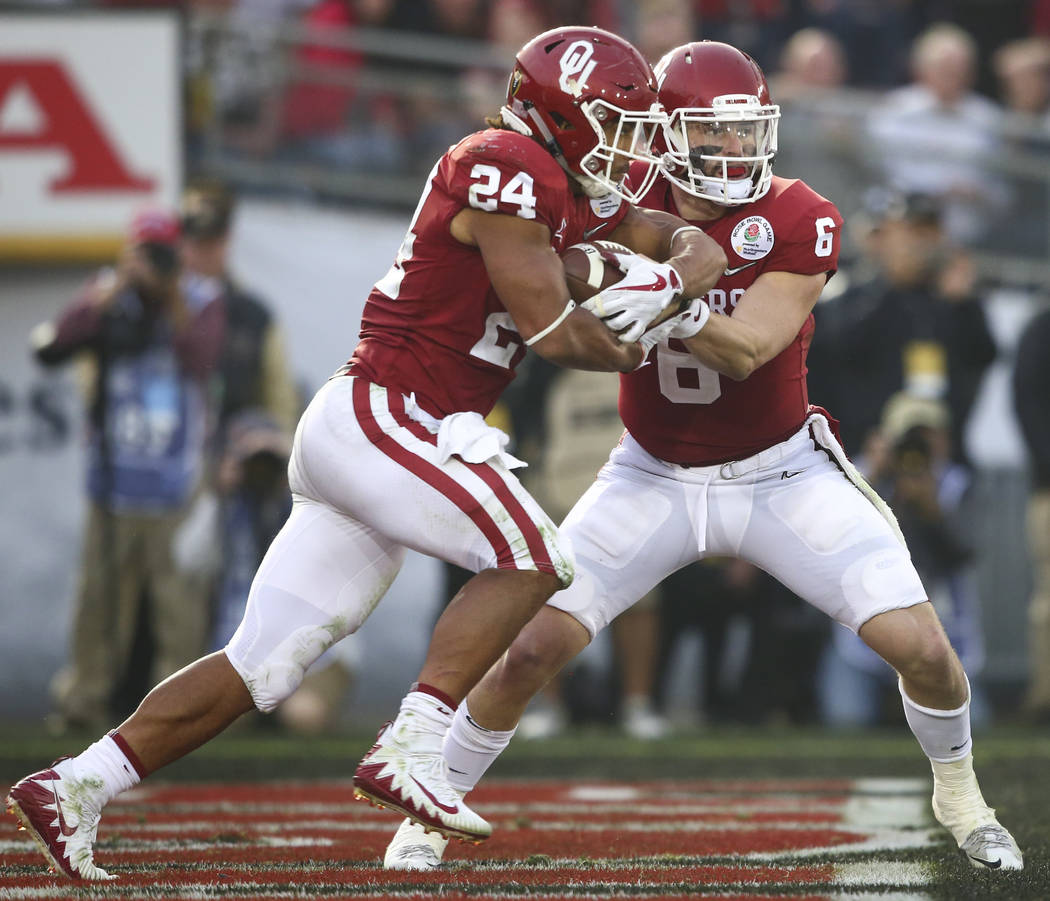 Oklahoma Sooners quarterback Baker Mayfield (6) hands off the ball to Oklahoma Sooners running back Rodney Anderson (24) during the second half of the College Football Playoff semifinal against th ...