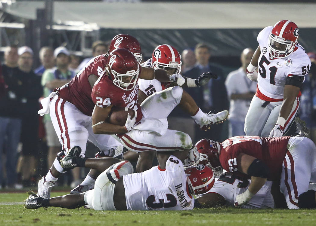 Oklahoma Sooners running back Rodney Anderson (24) gets tripped up by Georgia Bulldogs defense during the second half of the College Football Playoff semifinal at the Rose Bowl in Pasadena, Calif. ...