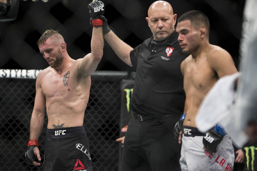 Tim Elliott, left, is announced the winner against Mark De La Rosa in the second round of the bantamweight bout during UFC 220 at T-Mobile Arena in Las Vegas, Saturday, Dec. 30, 2017. Elliott won  ...