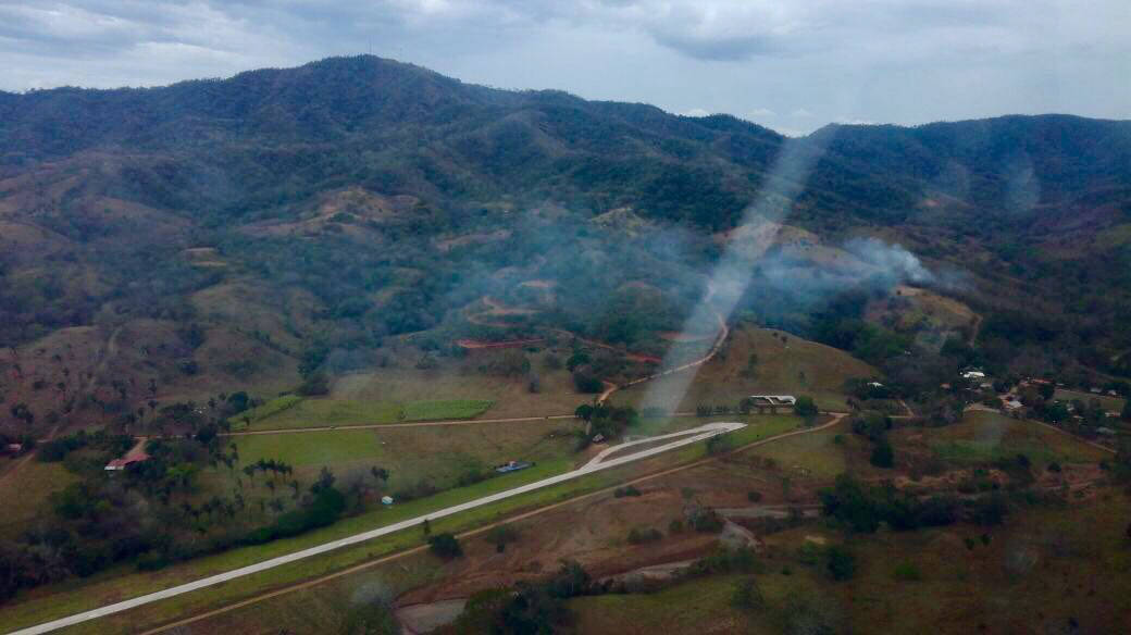 This photo released by Costa Rica's Public Safety Ministry shows smoke rising from the site of a plane crash near an air strip in Punta Islita, Guanacaste, Costa Rica, Sunday, Dec. 31, 2017. A gov ...