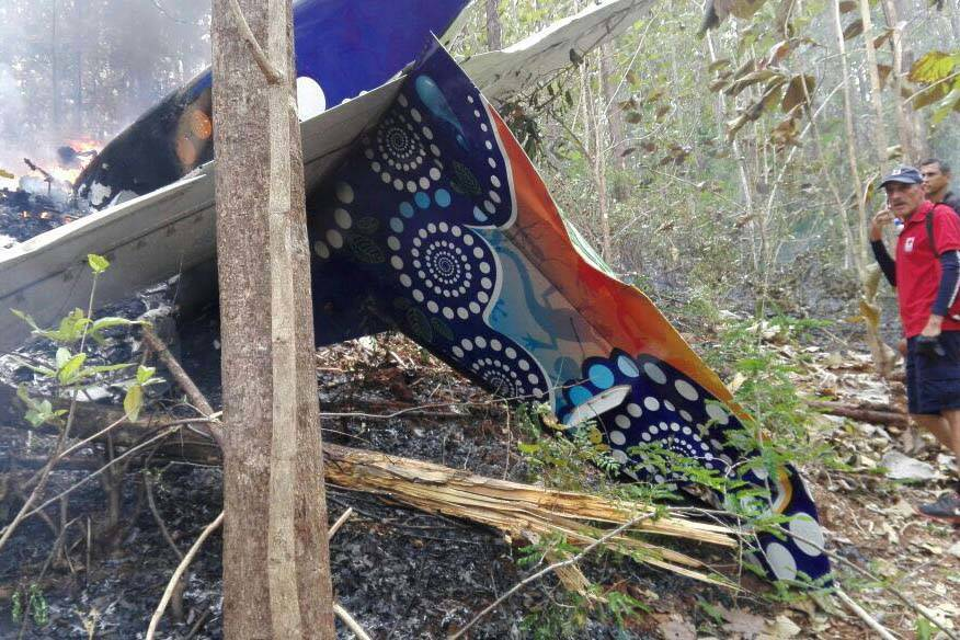 This photo released by Costa Rica's Public Safety Ministry shows people standing at the site of a plane crash near in Punta Islita, Guanacaste, Costa Rica, Sunday, Dec. 31, 2017. A government stat ...