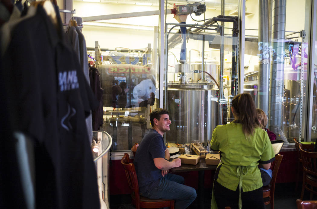 Sous chef Jaimie Fisher of Food Junky delivers food to Scott and Julie Jackson of Mason City, Ill. at Banger Brewing in downtown Las Vegas on Friday, Dec. 29, 2017. Food Junky, which recently bega ...