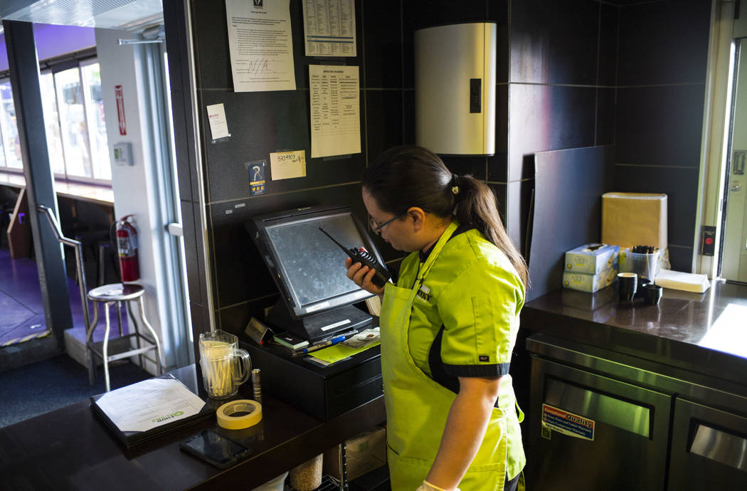 Chef Maritza Purcell, owner and operator of Food Junky, uses a walkie-talkie to communicate and receive orders from inside Inspire Theater in downtown Las Vegas on Friday, Dec. 29, 2017. Food Junk ...