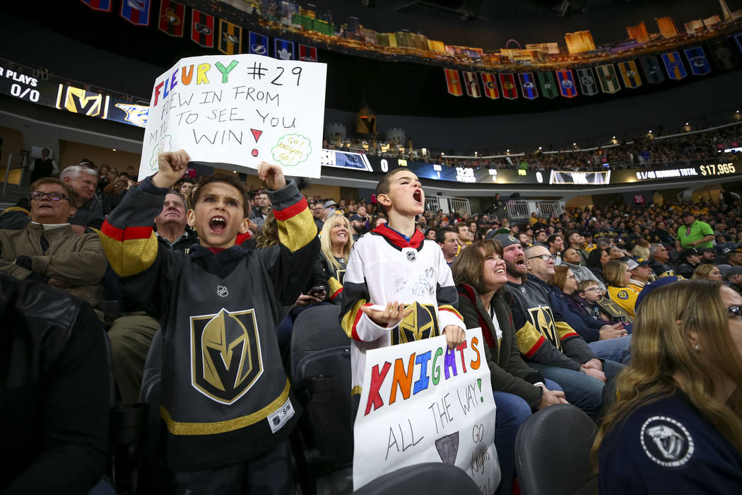 Golden Knights fans Nico Carlomusto, 7, and his brother, Luca, 10, visiting from Montreal, cheer during the first period of an NHL hockey game between the Vegas Golden Knights and the Nashville Pr ...