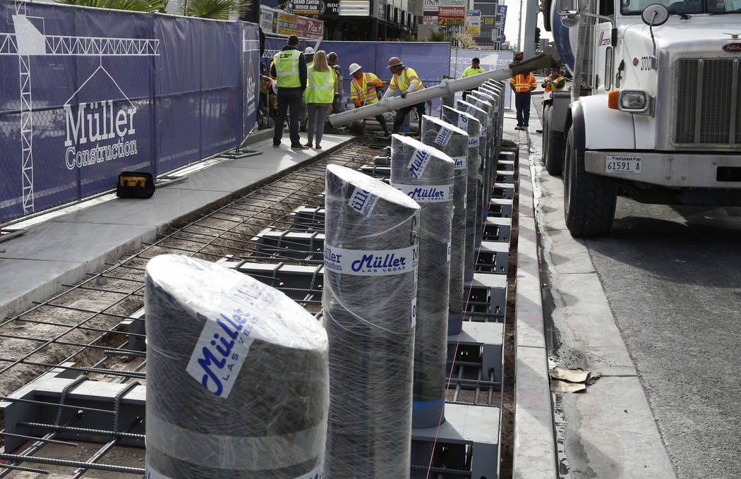 Construction crews pour cement where they began installing steel posts on the Las Vegas Strip near Aria on Monday, Nov. 13, 2017, to protect pedestrians along Las Vegas Boulevard. (Bizuayehu Tesfa ...