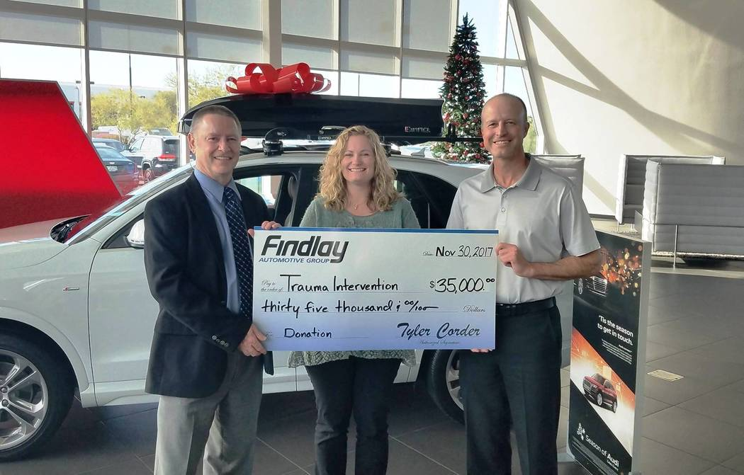 Findlay Automotive Findlay Automotive Group CFO Tyler Corder, left, and Findlay Automotive Group Director of Operations Justin Findlay, right, present a check for $35,000 to Jill Roberts, CEO of T ...