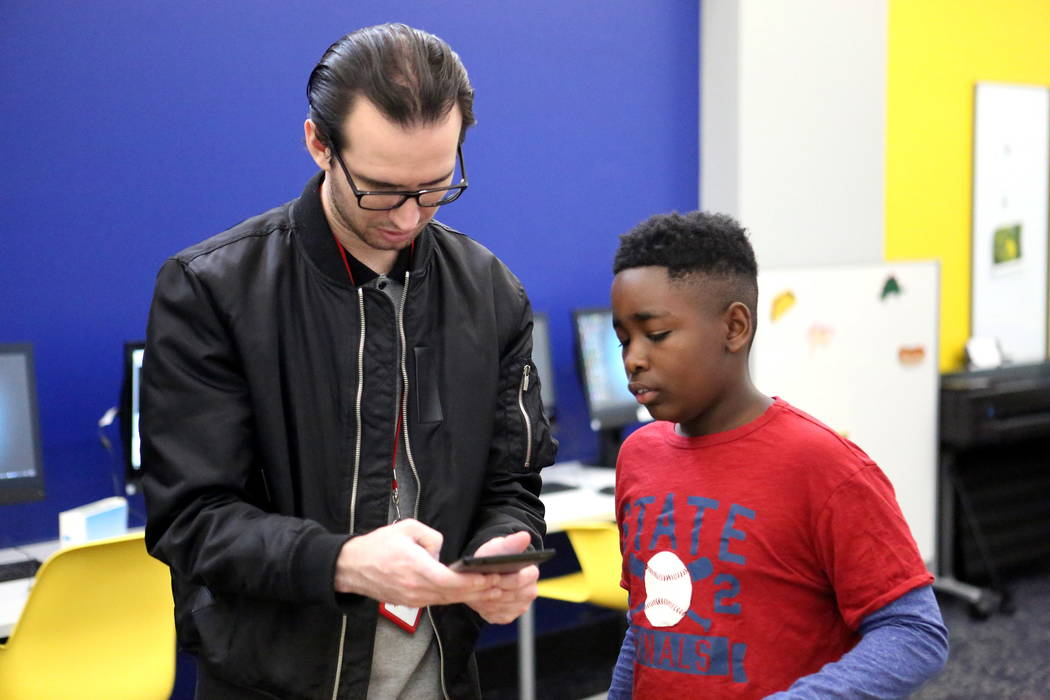 Teen Service Specialist Jake Duncan, 25, assists Frank Williamson, 13, with a mobile device app at the Clark County Library's Teen Tech Center which gives kids access to high-tech electroni ...