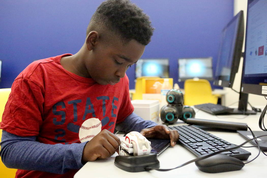 Frank Williamson, 13, learns how to program a small robot at the Clark County Library's Teen Tech Center which gives kids access to high-tech electronics and other materials with a science/ ...