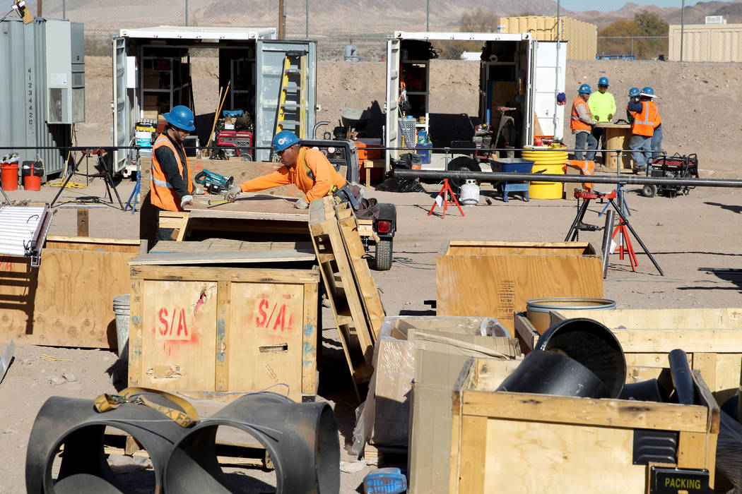Workers make boxes to ship pumps and other supplies after completing construction on a groundwater extraction and treatment system near the Pabco Trailhead at the Las Vegas Wash Thursday, Jan. 4,  ...
