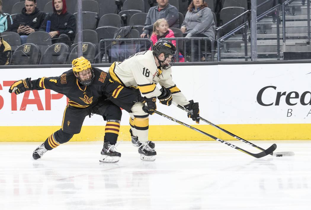 Arizona State Sun Devils defenseman Jacob Wilson (4) attempts to take the puck from Michigan Tech Huskies forward Greyson Reitmeier (18) during the inaugural Ice Vegas Invitational college hockey  ...