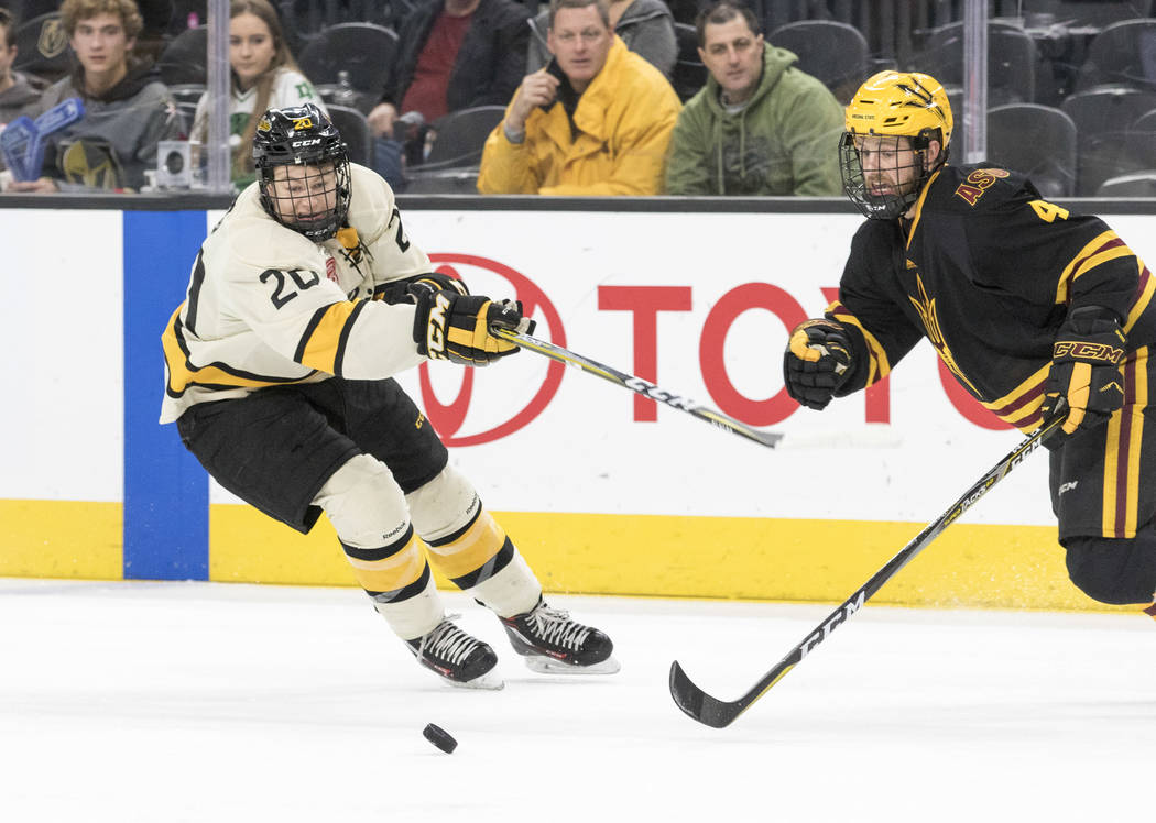Michigan Tech Huskies forward Alex Smith (20) and Arizona State Sun Devils defenseman Jacob Wilson (4) chase the puck during the inaugural Ice Vegas Invitational college hockey tournament at T-Mob ...