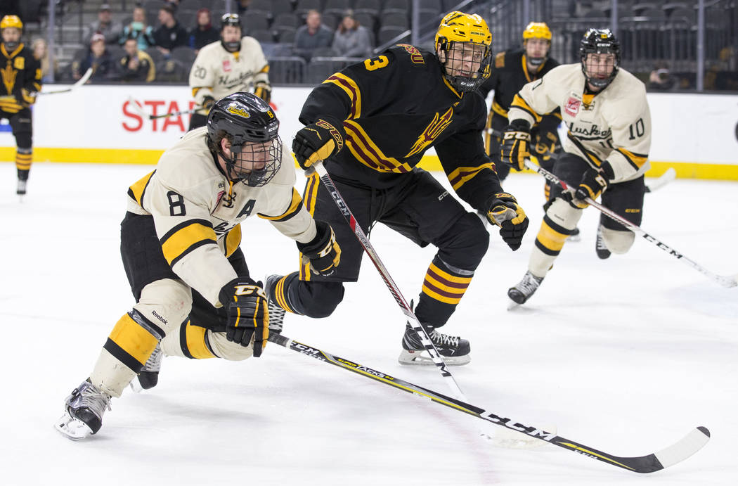 Michigan Tech Huskies forward Dylan Steman (8) and Arizona State Sun Devils defenseman Gvido Jansons (3) chase the puck during the inaugural Ice Vegas Invitational college hockey tournament at T-M ...