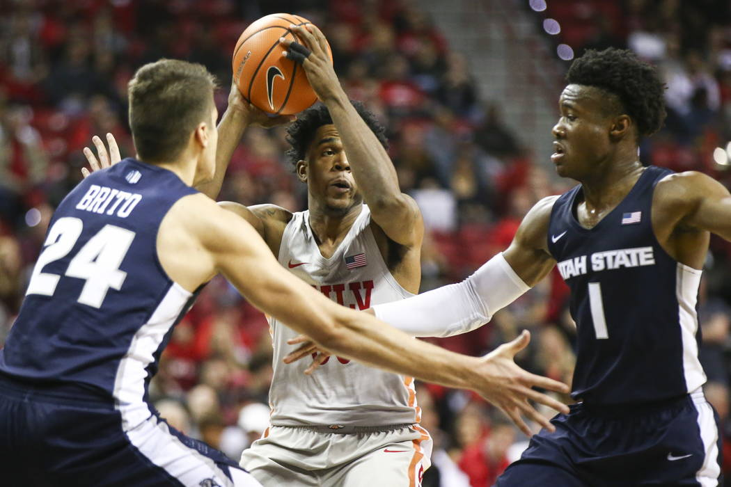 Utah State Aggies guards Diogo Brito (24) and Koby McEwen (1) defend as UNLV Rebels guard Jovan Mooring (30) looks to pass during the first half of a basketball game at the Thomas & Mack Cente ...