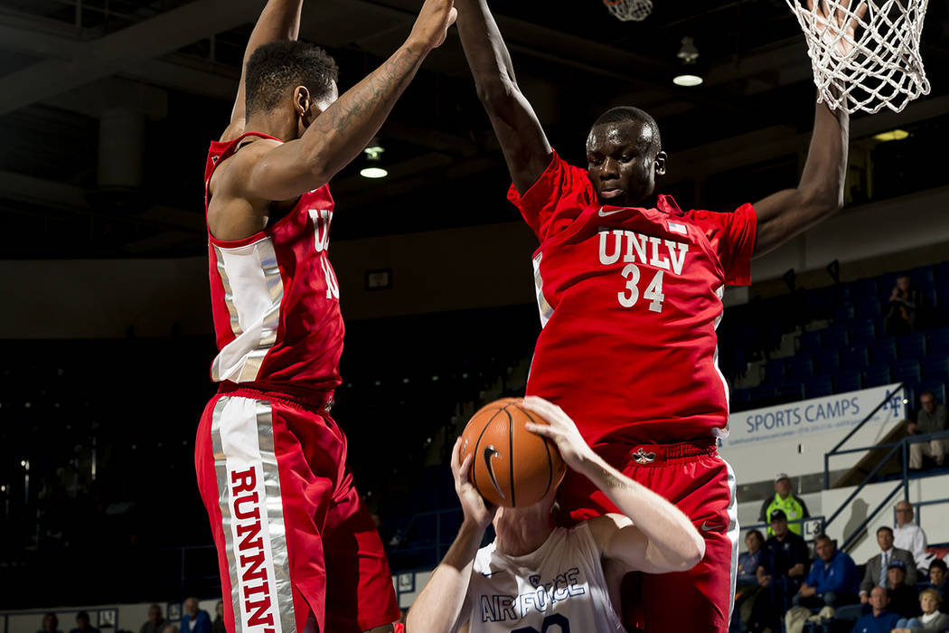 Air Force center Frank Toohey is blocked on his basket attempt by UNLV forwards Shakur Juiston, left, and Cheikh Mbacke Diong (34) during an NCAA college basketball game at Air Force Academy, Colo ...