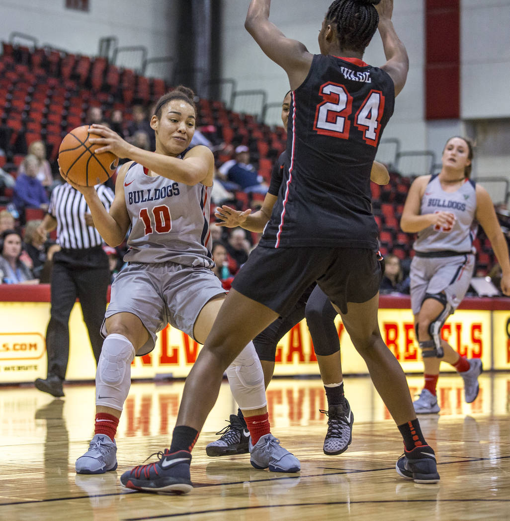 Fresno State's Candice White (10) looks for a pass while UNLV's Rodjanae Wade (24) tries to block her at Cox Arena in Las Vegas on Wednesday, Jan. 24, 2018. Fresno State won 74-72.  Patrick Connol ...