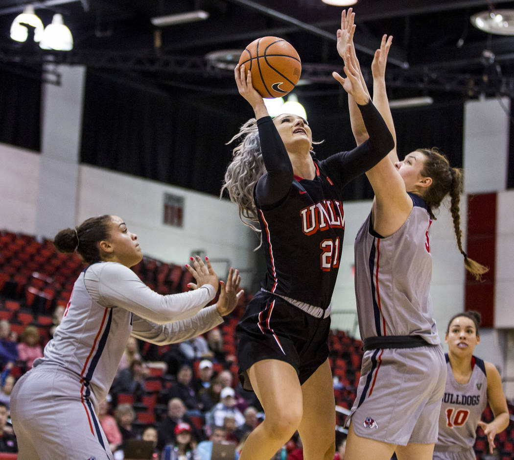 UNLV's Katie Powell (21) goes up for a shot while Fresno State's Jordanna Porter (14), left, and Katelin Noyer (5) try to block her at Cox Arena in Las Vegas on Wednesday, Jan. 24, 2018. Fresno St ...