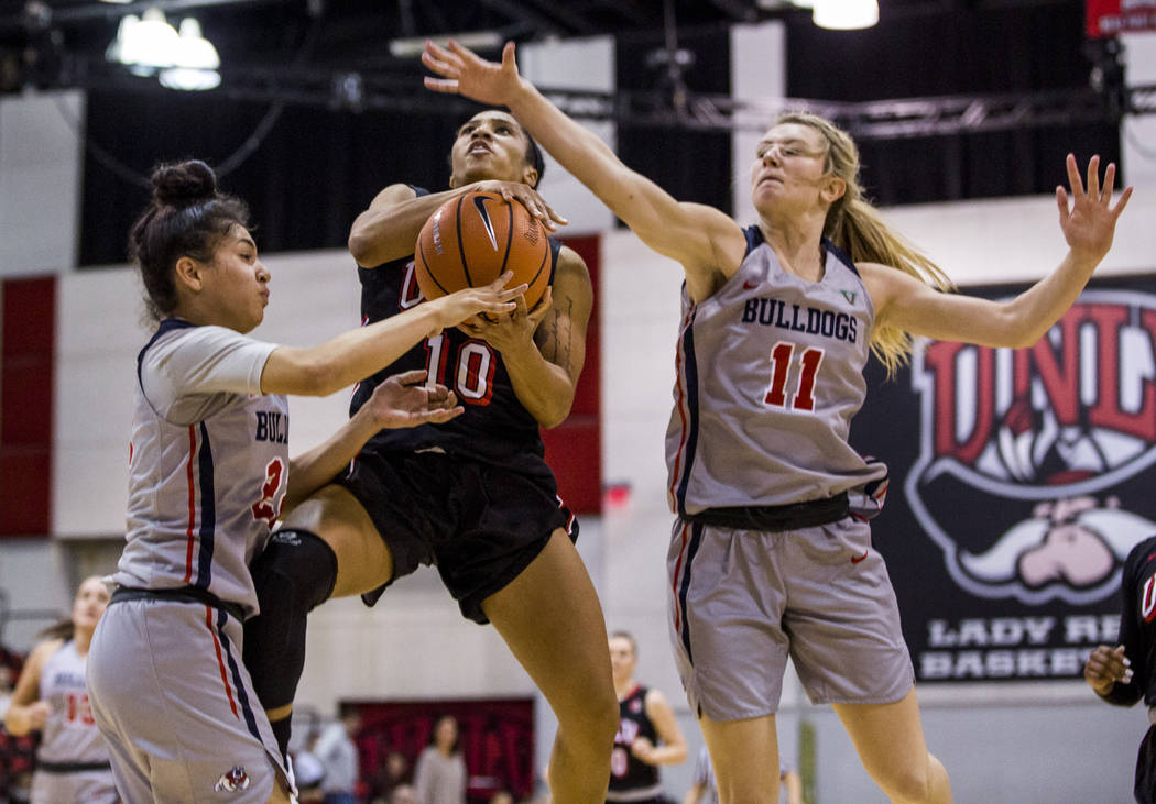 UNLV's Nikki Wheatley (10) goes up for a shot while Fresno State's Maddi Utti (11) and Aly Gamez (22) try to block her at Cox Arena in Las Vegas on Wednesday, Jan. 24, 2018. Fresno State won 74-72 ...