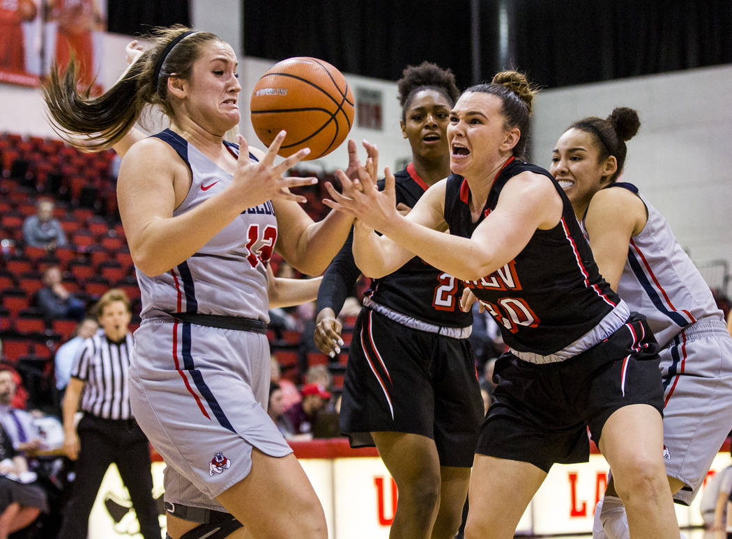 UNLV's Alyssa Anderson (20) and Fresno State's Breanne Knishka (13) grapple over the ball while UNLV's Jordyn Bell (23) and Candice White (10) watch the action at Cox Arena in Las Vegas on Wednesd ...