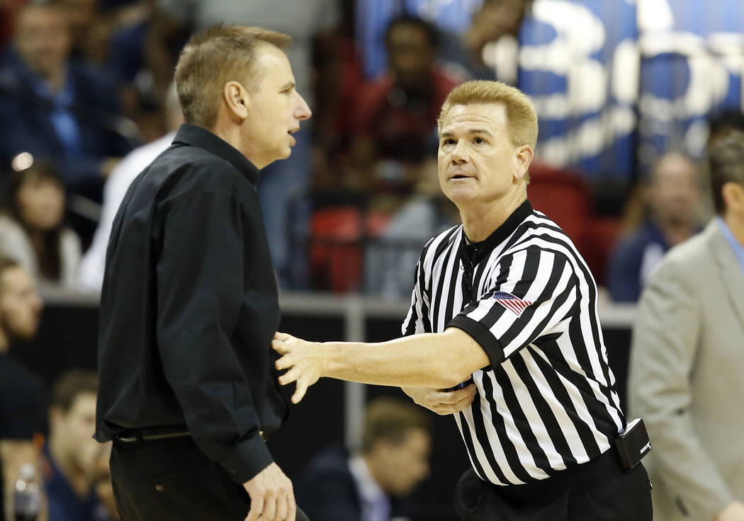 Official Larry Spaulding holds back Colorado State coach Larry Eustache before calling a technical foul on him during the second half of the team's NCAA college basketball game against Nevada in t ...